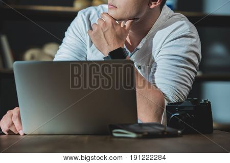 Cropped Shot Of Young Man Being Lost In Thought During Work On Laptop