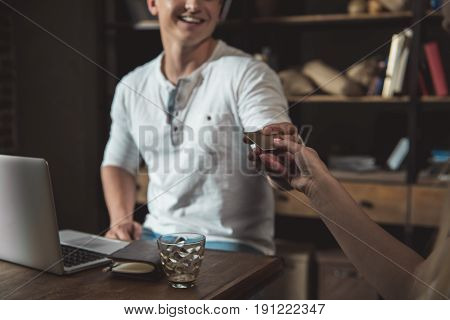 Portrait of stylish man paying with credit card in coffee shop