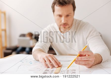 Concentrate on it. Serious engineer wrinkling his forehead and holding ruler on the sketch while going to measure details again