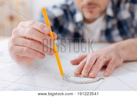 Take protractor. Competent in architecture man sitting at his workplace holding pencil in right hand while drawing circle