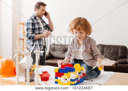 Casual style. Serious man standing on the background and having telephone call while actively gesticulating