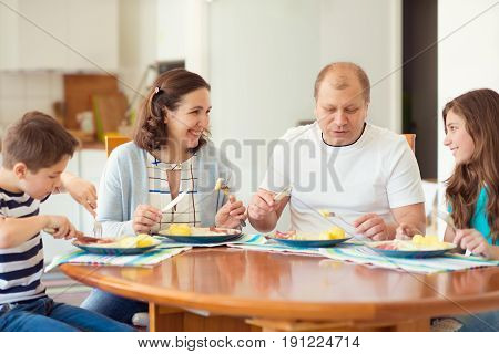 Happy Family Enjoying Dinner At Home. Mother, Father, Daughter, Son