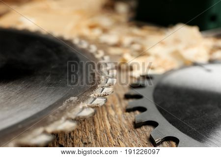 Circular-saw disks on wooden table in carpenter's workshop, closeup