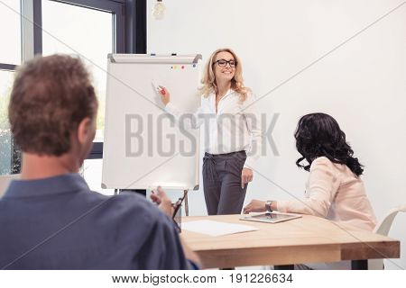 Smiling businesswoman in eyeglasses pointing at blank whiteboard and looking at colleagues during presentation