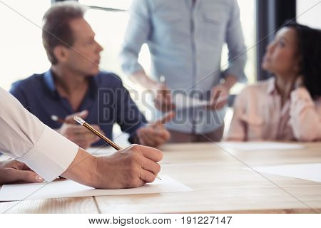Cropped Shot Of Woman Making Notes At Business Meeting In Office