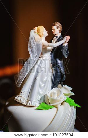 close up of a wedding cake topper in shape of dancing bride and groom