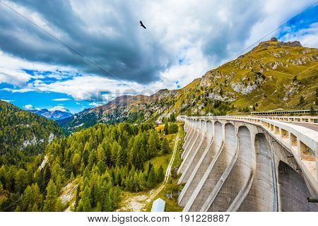 Mountain Lake Lago di Fedaia, Dolomites. Powerful dam blocked the lake. The concept of ecological and extreme tourism