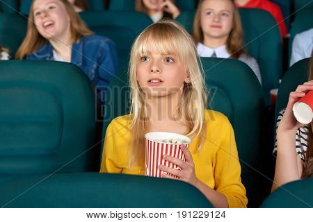 Shot of a cute young blonde haired girl watching a movie at the cinema looking fascinated children kids entertaining activity weekend holidays amazement amusement films activity concept.