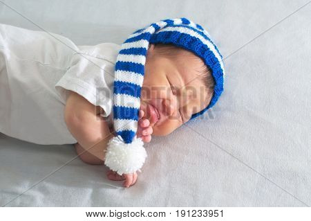 newborn in hat on white blanket asian baby stomach ache. Infant care teething pain colic ache concept