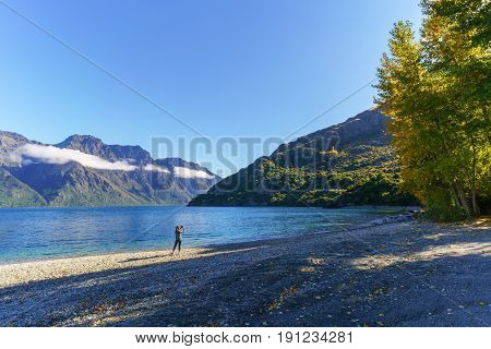 Young Asain woman taking picture of beautiful Lake Wakatipu South Island of New Zealand