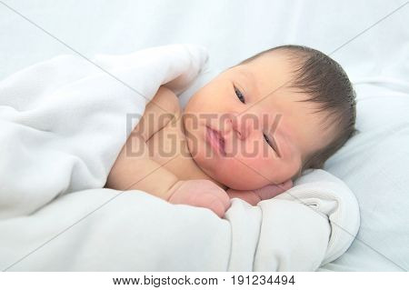 Newborn jaundice baby portrait in blanket, infant care concept