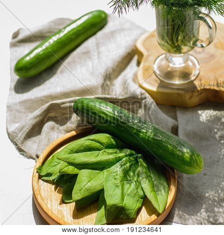 fresh green cucumbers spinach leaves and dill served on a wooden background