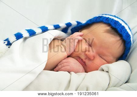 happy baby face in hatnewborn with jaundice on white blanket infant healthcare concept