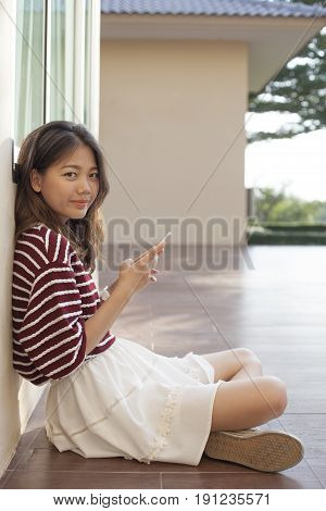 asian woman using smart phone in hand looking with eyes contact