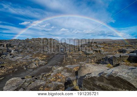 Rainbow over a fott path in Iceland