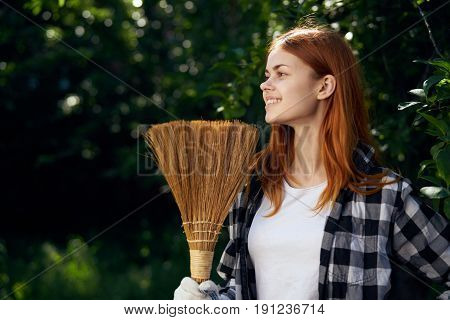 Young woman with broom, woman holding a broom, woman smiling, giving, kitchen garden.