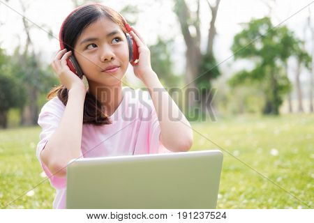 Relax And Listen Music Concept. Girl With Wireless Headphones Listens To The Music In Park.