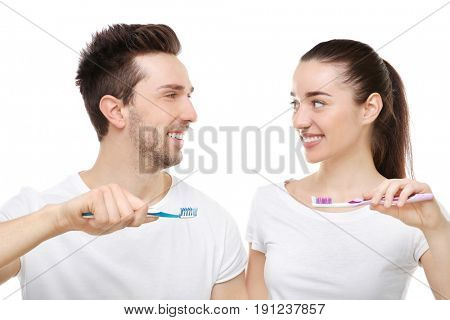 Young happy couple brushing their teeth on white background