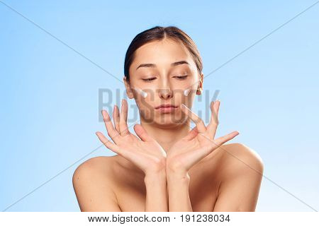 Beautiful woman, clean skin, face with cream, woman applied cream on face, woman on blue background.