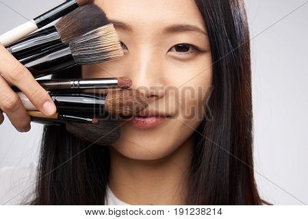 Beautiful asian woman holding a cometic brush portrait on a gray background.