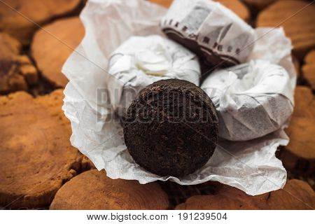 Round extruded briquettes of puerh tea on wooden background stand