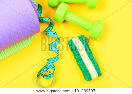 Dumbbells And Headband Near Twisted Measuring Tape And Yoga Mat