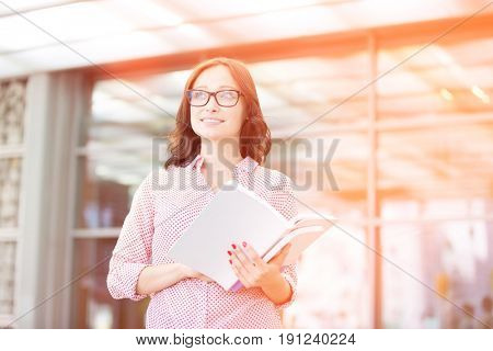 Smiling woman looking away while holding outside building