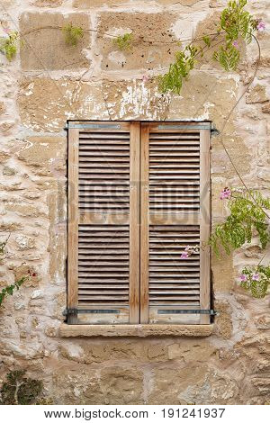 Window with wooden shutters in an old building close-up