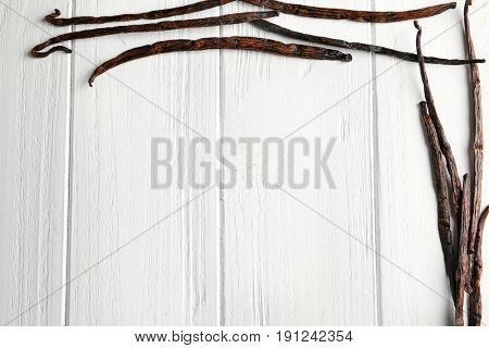 Composition with dried vanilla sticks on light wooden table
