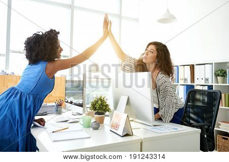 Profile view of cheerful young businesswomen giving high five after successful project completion, panoramic windows of open plan office on background