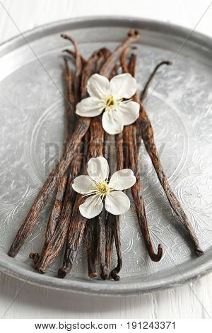 Metal plate with dried vanilla sticks and flowers on light wooden table, closeup