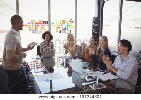 Business people applauding for colleague giving presentation in office