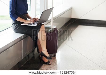 Low  section portrait of beautiful businesswoman  using laptop in airport while waiting for plane with big suitcase