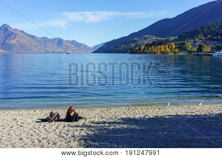 Two young women relaxing on the beach of Lake Wakatipu Queenstown South Island of New Zealand