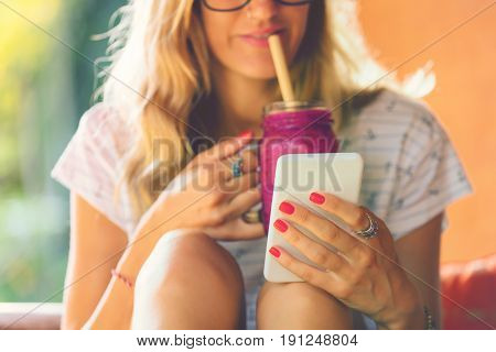 Attractive cute girl using cellphone and drinking smoothie outdoors.