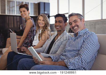 Portrait of smiling business people sitting together on sofa while holding technologies at creative office