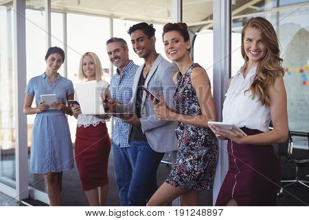 Portrait of creative business team using technologies while standing together at office