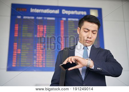Portrait of handsome Asian businessman checking time on wristwatch while waiting for his flight in airport, standing against departure board