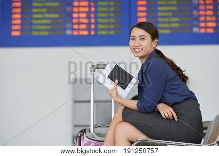 Side view portrait of smiling Asian woman looking at camera while waiting for departure  in airport with big suitcase and passport