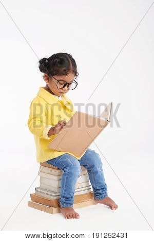 Cute little bookworm in eyeglasses sitting on pile of books and reading encyclopedia with interest, isolated on white background
