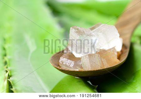 Aloe Vera Gel In Wooden Spoon With Aloe Vera Leaves Background.