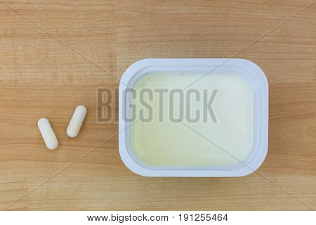 Top view of low fat Yogurt next to white Yoghurt capsules containing cultures to help with digestive system, on wooden background