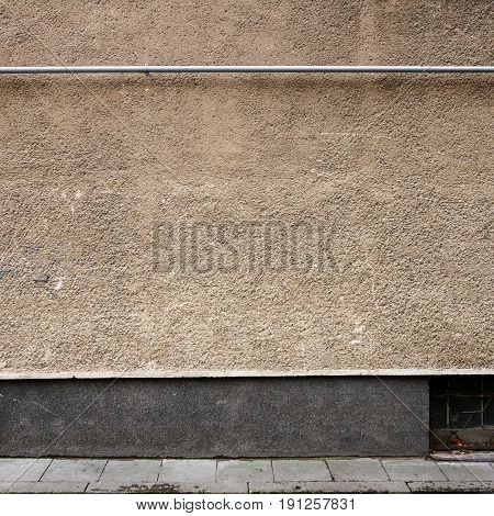 Old weathered plaster wall and a sidewalk. Architecture detail background