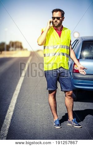 Grumpy man in reflective vest on the road, talking with insurance company after a car breakdown.