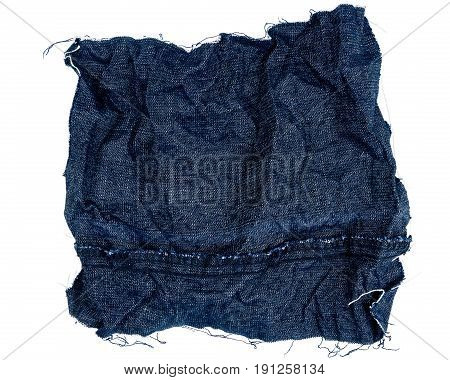 Piece of crumpled blue jeans fabric isolated on white background. Rough uneven edges. Wrong side of fabric