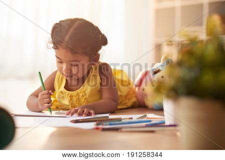 Mixed race little girl lying on floor and drawing picture with colored pencil, portrait shot