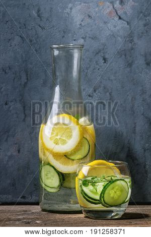 Citrus cucumber sassy sassi water for detox in glass bottle on wooden blue background. Clean eating, healthy lifestyle concept, sunlight