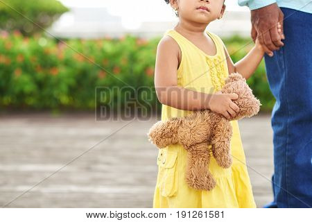 Close-up shot of unrecognizable little girl in yellow dress holding teddy bear in hand while having walk with her dad in summer park