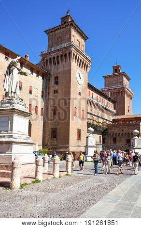 Ferrara Italy - July 21 2011: Visitors near the Estense castle with the Savanarola monument on the left