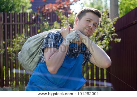 Caucasian gardener in overalls and working gloves carrying bag with garbage in summer day